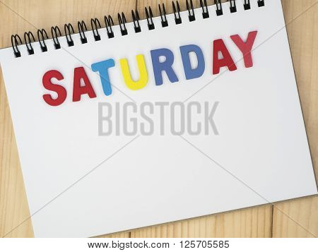 Saturday word spell by wooden letters on blank notebook with wood background (Weekdays word series)