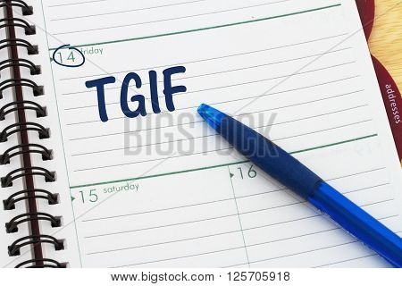 Happy it is Friday a day planner with blue pen with text TGIF