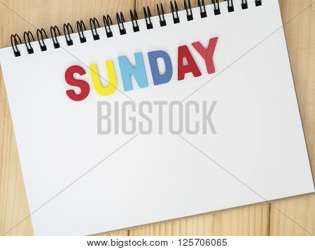 Sunday word spell by wooden letters on blank notebook with wood background (Weekdays word series)