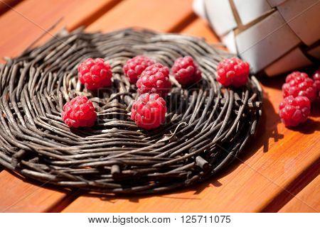 fresh raspberry in a basket on wooden table sunlight