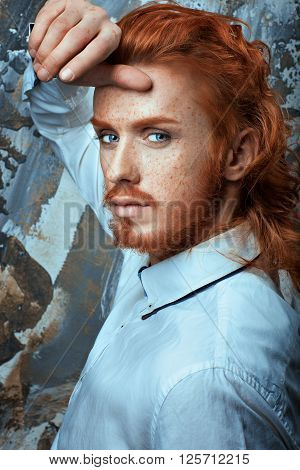 Red-haired man with a beard and mustache in a white shirt metrosexual.
