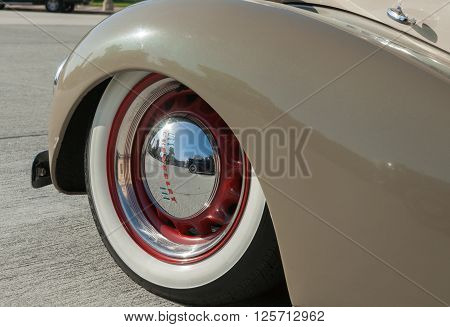 Pasadene, USA - October 4, 2015: American vintage car wheel close up with lens flare on shiny hubcap reflections of Packard and brand Chevrolet