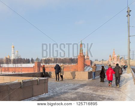Moscow - January 7 2016: People walk by and large Moscow River bridge and see the Kremlin Ivan the Great Bell Tower and St. Basil's Cathedral winter day January 7 2016 Moscow Russia