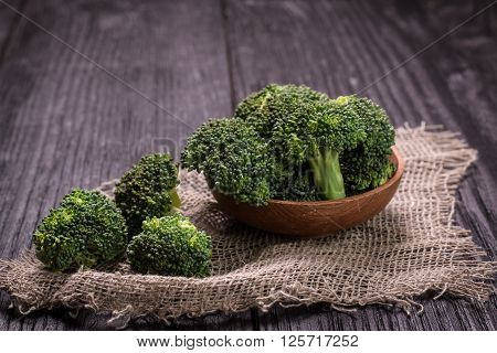 Bunch of fresh green broccoli on brown plate over wooden background poster