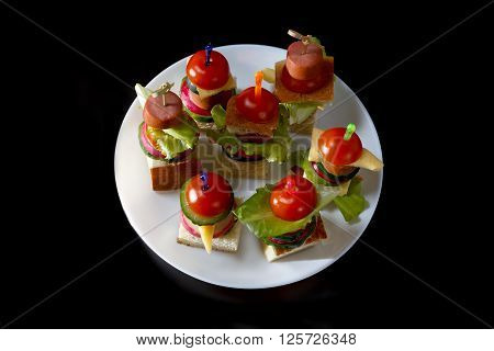 Small snacks canape with cherry tomatoes cheeze sausages and vegetables on bread on skewers on white plate against black background horizontal overhead view