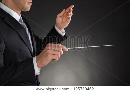 Person Directing With A Conductor's Baton On Grey Background poster