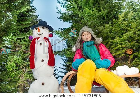 Funny girl in a grey knitted hat and warm scarf playing with a snowman