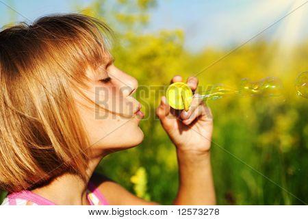 Little girl blowing soap bubbles