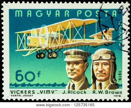 MOSCOW RUSSIA - APRIL 12 2016: A stamp printed in Hungary shows aviators John Alcock and Arthur Whitten Brown with airplane Vickers