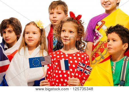 Portrait of six children wrapped in flags of USA and European nations holding pennons of EU, USA, France and UK, isolated on white