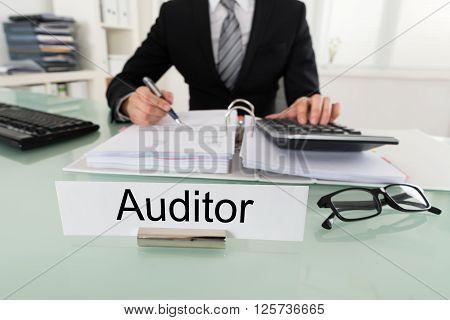 Male Auditor Calculating Bill