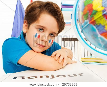 French schoolboy learning geography with the globe at the classroom - bonjour is hello in French