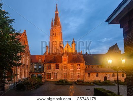 Night view on yard of Our Lady Church by twilight and setting sun in Bruges Belgium. poster