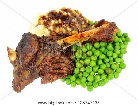 Slow cooked lamb shank meal with mashed potato and peas isolated on a white background