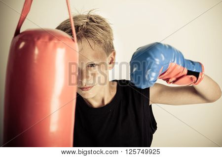 Boy Swings Single Gloved Hand At Red Punching Bag