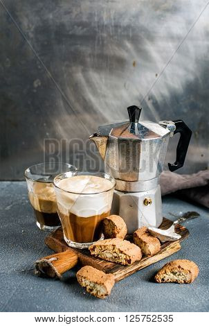 Glass of latte coffee on rustic wooden board, cantucci biscuits and steel Italian Moka pot, grey background, selective focus, copy space