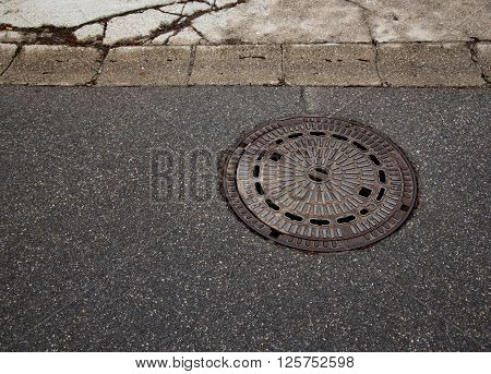 Abstract manhole cover on asphalt pavementin Germany