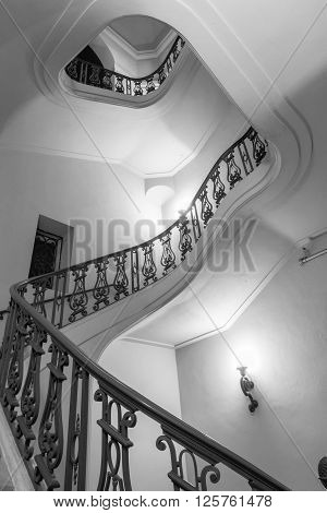 Light and shade in internal stairwell with banister winding to top