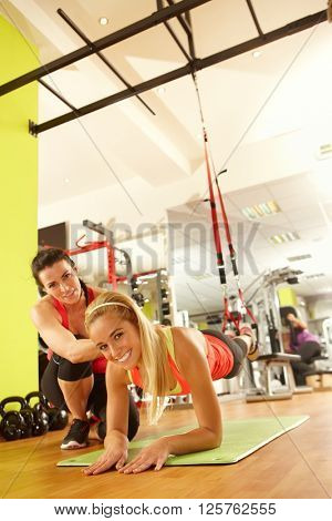 Sporty young woman doing suspension training with personal trainer in gym.