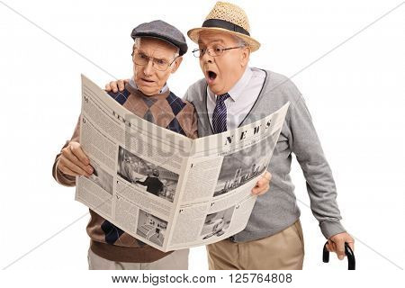 Two baffled senior gentlemen reading a newspaper isolated on white background