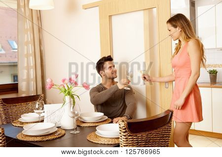 Young couple having dinner at home with friends, clinking glasses.