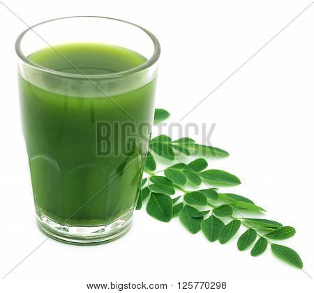 Moringa leaves with juice in a glass over white background