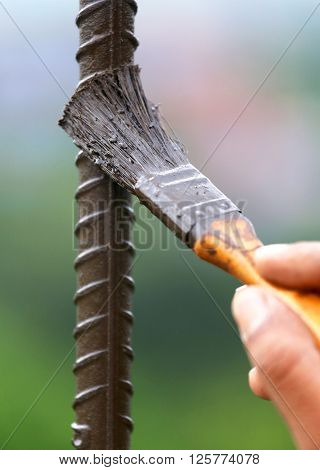 Painting an iron rod with a brush outdoor