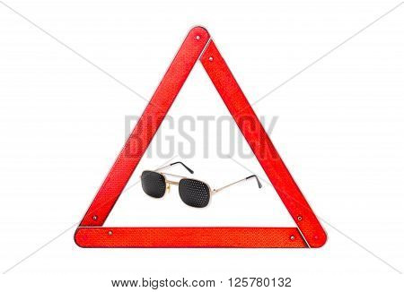 Pinhole glasses among warning triangle sign with red border on a light background