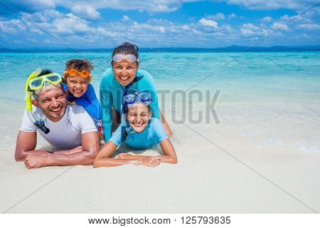 Photo of happy family of divers looking at camera during summer vacation on the tropical white beach