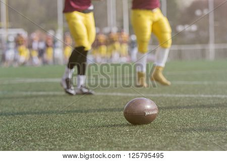 Ball and American football players on the green grass field