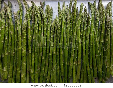 An above view of asparagus seasoned with salt and pepper on a metal roasting pan.