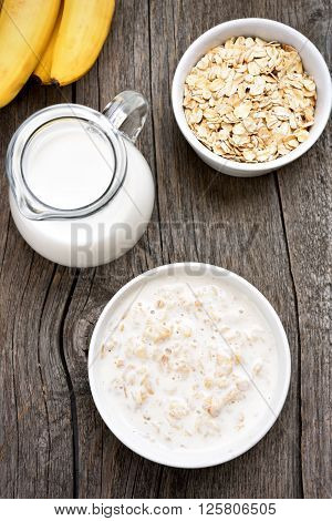 Oatmeal oats in bowl and jug of mik on wooden background top view
