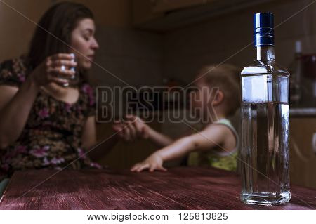 Drunk mother with alcoholic drink scolding her little son. Female alcoholism. Focus on bottle. poster