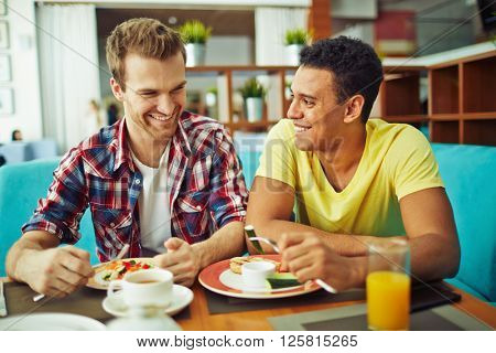 Male friends having lunch in cafe together