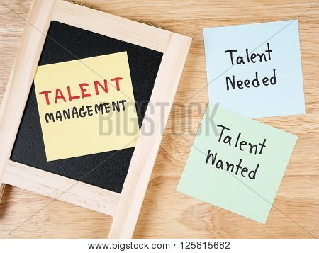 Handwriting Talent Management Talent Needed Talent Wanted on colorful note paper and notebook with wood background.