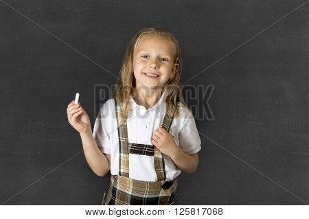 young sweet junior schoolgirl with blonde hair standing and smiling happy isolated in blackboard background holding chalk wearing school uniform in children education success and fun