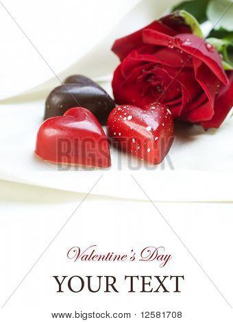 Valentinskarte.Schokoladen Herzen und rote rose