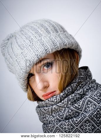 Young sullen ill woman in scarf and hat