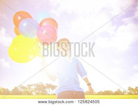 Happy Boy Outdoors With A Dozen Of Helium Balloons Concept