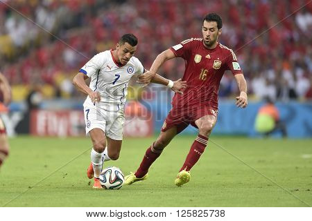 RIO DE JANEIRO BRAZIL - June 18 2014: Alexis SANCHEZ of Chile and Sergio BUSQUETS of Spain during the FIFA 2014 World Cup. Spain is facing Chile in the Group B at Maracana Stadium