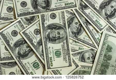 Background texture of banknotes in denominations of one hundred dollars scattered on a table