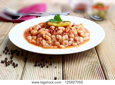 White beans stewed in tomato sauce on white background