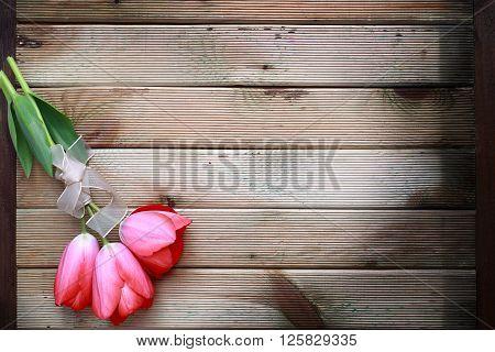 red tulip bouquet on dark wooden background