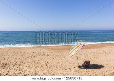 Beach blue ocean horizon with holiday bather swimming coastline landscape.