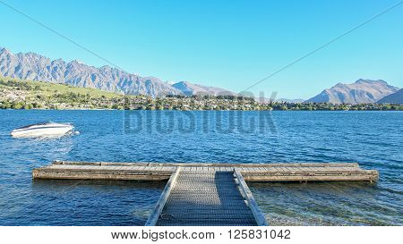 A white boat is anchoring around a T-shaped pier on blue Lake Wakatipu Queenstown New Zealand.