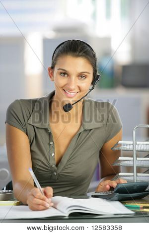 Portrait of a young woman smiling sitting at a desk with a headset