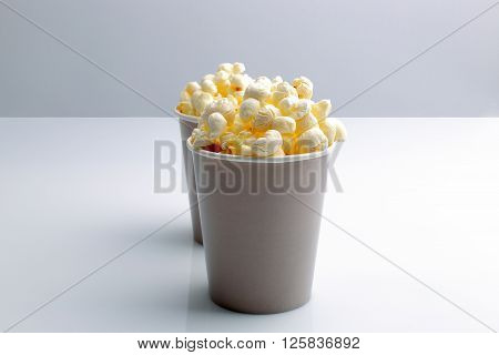 Brown tall bowl with popcorn isolated on white