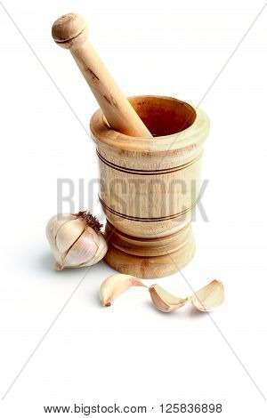 Wooden mortar with healthy dried garlic on white background