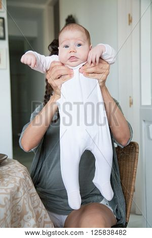 portrait of two month age baby white onesie shirt open eyes funny expression face stretched in hands of brunette woman mother with grey shirt and pigtails sitting indoor