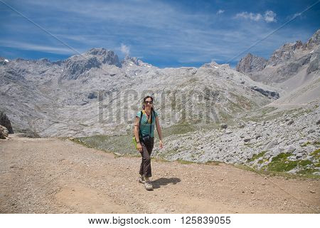 brunette sport smiling happy woman with green shirt brown trousers walking or hiking or trekking on rural path in Picos de Europa mountains in Cantabria Spain